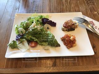 木製のテーブルの上に食べ物のプレートの写真・画像素材[1170286]