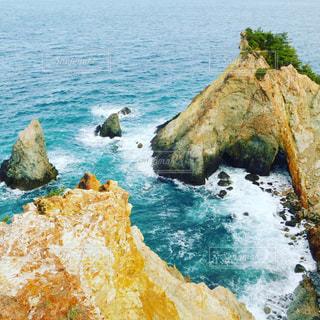 水の体の横にある岩の上の人々 のグループの写真・画像素材[1170848]