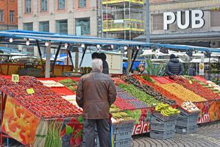 果物の屋台の前に立っている男の写真・画像素材[1172942]