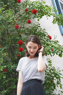 花の前に立っている女性の写真・画像素材[1239623]