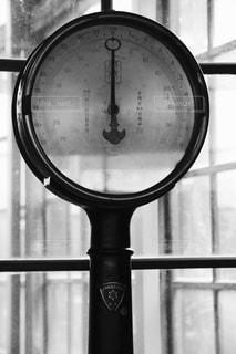 ウィンドウの端からぶら下がっている時計の写真・画像素材[1173952]
