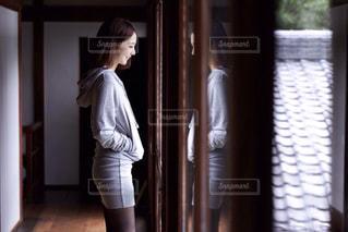 ウィンドウの前に立っている女性の写真・画像素材[811611]