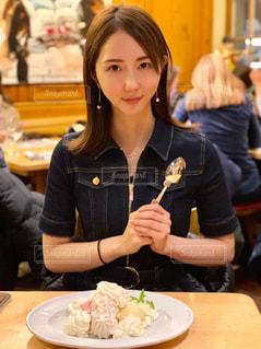 食べ物の皿を持ってテーブルに座っている女性の写真・画像素材[3076003]