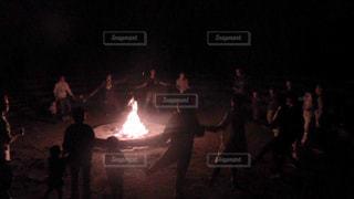 火の周りを囲んでキャンプファイヤーのマイムマイムを楽しんでいる人々 のグループの写真・画像素材[1174344]