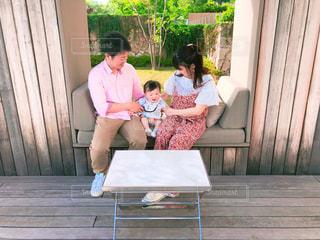オシャレなカフェのベンチで家族写真撮影。の写真・画像素材[1177709]