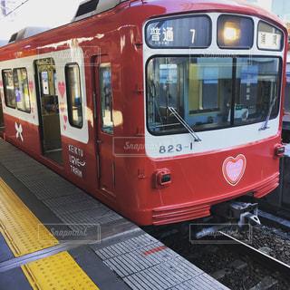 赤い客車列車が駅で停止の写真・画像素材[1179125]