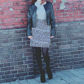 レンガ壁の前に立っている女性の写真・画像素材[1737343]