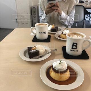 コーヒーを飲みながらテーブルに座っている人の写真・画像素材[2975626]