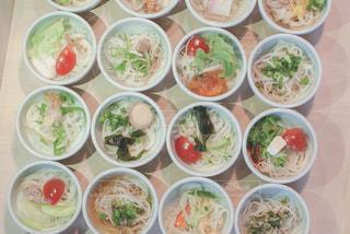 テーブルの上に食べ物の多くの異なる種類で満たされたボウルの写真・画像素材[1181557]
