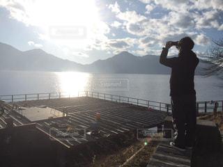 桟橋の前に立っている男の写真・画像素材[1187797]
