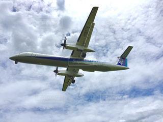 曇りの日に空を飛んでいる飛行機の写真・画像素材[1280887]