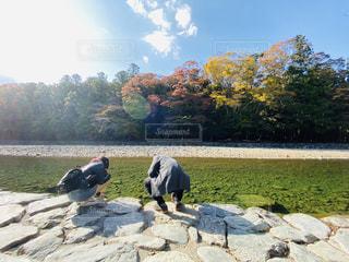 湖の隣に立っている人々のグループの写真・画像素材[2737871]