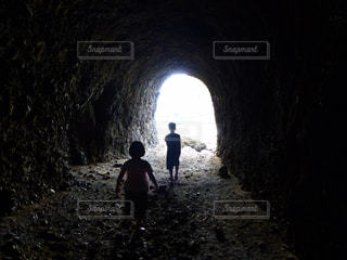 暗いトンネルの中に立っている男の人の写真・画像素材[1013072]