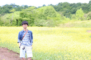 草の覆われてフィールド上に立っている人の写真・画像素材[1201402]