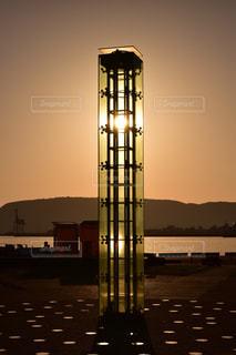 水の体の上にそびえ立つ大きな時計塔の写真・画像素材[1194874]