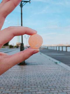 オレンジ飴と手の写真・画像素材[1221830]