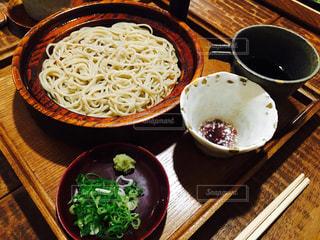 木製テーブルの上に座って食品のボウルの写真・画像素材[1201608]