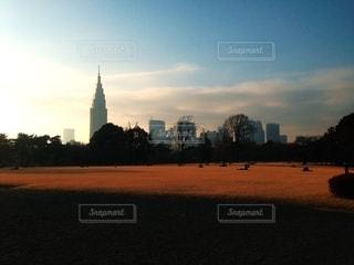 バック グラウンドで市と水体に沈む夕日の写真・画像素材[1265553]