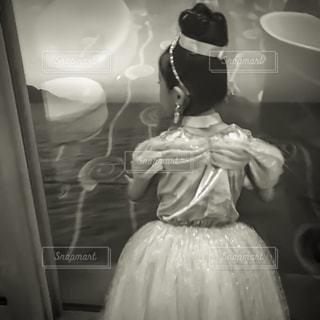 窓辺で海を眺める立つドレス姿の女の子の写真・画像素材[1206020]