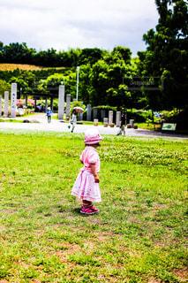 芝生に佇む女の子の写真・画像素材[1211197]