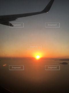 日没の前に飛んでいる飛行機の写真・画像素材[1197834]