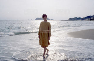 水の体の近くのビーチに立っている人の写真・画像素材[728898]