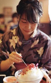 食品のプレートをテーブルに座っている女性の写真・画像素材[728900]