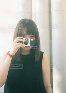 カメラにポーズを鏡の前で彼女の歯を磨く女性の写真・画像素材[765036]