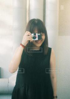 カメラにポーズ鏡の前に立っている女性の写真・画像素材[765037]