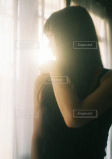 ウィンドウの前に立っている女性の写真・画像素材[797444]
