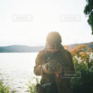 湖の隣に立っている男の写真・画像素材[915962]