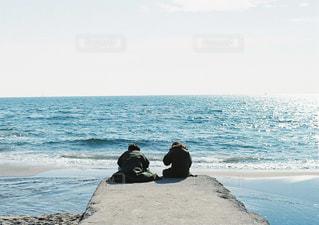 海の横にあるビーチの上を歩く男の写真・画像素材[1099870]