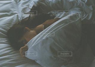 ベッドの上で眠っている人の写真・画像素材[1099880]