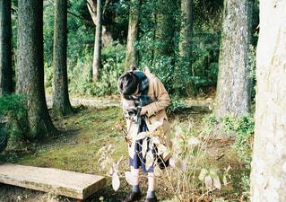 森林の隣に立っている男の写真・画像素材[1116640]