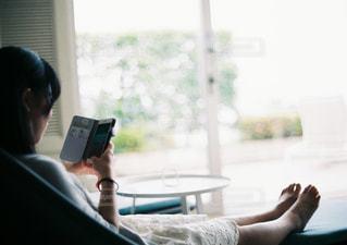 携帯電話で話している椅子に座っている女性の写真・画像素材[1248983]