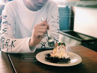 皿の上のケーキをテーブルに着席した人の写真・画像素材[1441022]