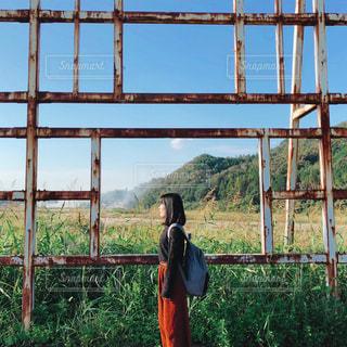 フェンスの前に立っている人の写真・画像素材[1525391]