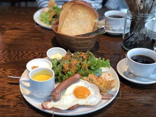 食品やコーヒー テーブルの上のカップのプレートの写真・画像素材[1553948]