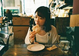 食べ物を食べながらテーブルに座っている女性の写真・画像素材[2425827]