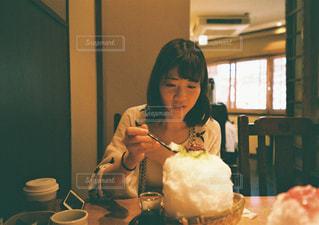 テーブルの上に座っているケーキを持っている女性の写真・画像素材[2425829]