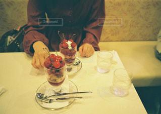 ワイングラスを持ってテーブルに座っている人の写真・画像素材[2425842]