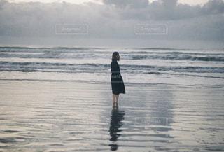 水の体の横に立っている人の写真・画像素材[1553018]