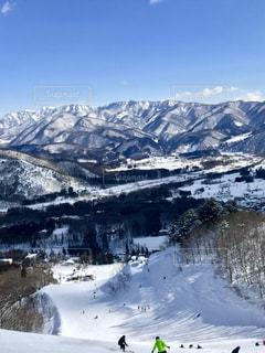 煙る山頂の雪の上にスキーに乗っている人のグループの写真・画像素材[1201561]