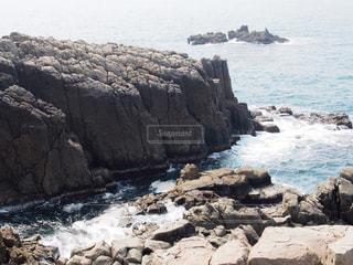 水の体の横にある岩のビーチの写真・画像素材[1200889]