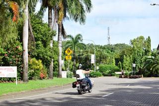 通りをバイクに乗った人の写真・画像素材[1208336]