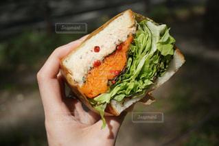 近くにサンドイッチを持っている手のアップの写真・画像素材[1322800]