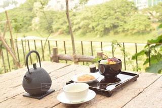 木製フェンスの上に座ってコーヒー カップの写真・画像素材[1322876]