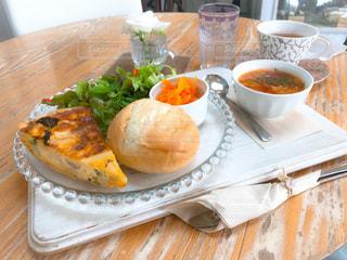 木製テーブルの上に座って食品のプレートの写真・画像素材[1324764]
