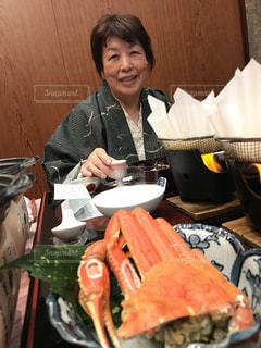 食事のテーブルに座っている女性の写真・画像素材[1215004]
