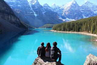 水と背景の山の前に立っている男の写真・画像素材[1219244]